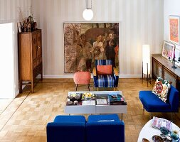 Blue retro easy chairs around display-case tables and painting on striped wallpaper in eclectic living room with mosaic parquet floor