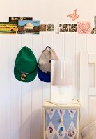 Table lamp on painted bedside cabinet below caps hung on white wainscoting with row of postcards on top
