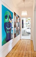 View along narrow hallway with rustic wooden floor and large modern artworks to gallery of pictures in living room