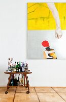 Home bar on fifties-style serving trolley below large modern painting on wall