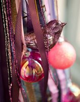 Silver bird, pink baubles and ribbons used as Christmas decorations