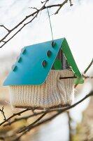 Vogelhäuschen mit Stricküberzug an Zweig aufgehängt