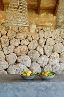 Two grey ceramic bowls of lemons on grey wall below basketwork lampshades in front of dry stone wall