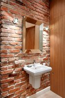 Vintage sink and mirror on rustic brick wall with modern wooden cabinet to one side
