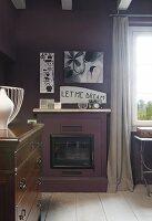 Auberginefarben getönte Wände im Wohnraum, über gemauertem Kaminofen geschriebene Botschaft