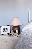 Table lamp with brass base and pink lampshade on stone bedside table against pastel wall