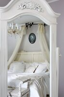 Mirror with white, carved wooden frame reflecting double bed with white bed linen and canopy