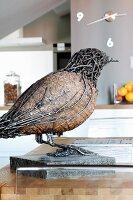 Metal bird figurine on stone slab
