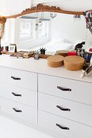 Mirror with carved frame, jewellery and make-up utensils on white chest of drawers