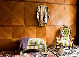 Floor-to-ceiling wardrobe with exotic-wood veneer, antique armchair and bench with yellow striped covers and dog in eclectic interior