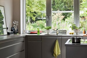 Grey L-shaped fitted kitchen with garden view