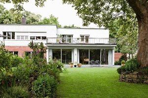 Herbaceous borders and lawn in back garden of white Bauhaus flat-roofed building