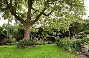 Deciduous tree, flowering herbaceous border, wooden artwork and black outdoor furniture in summery garden