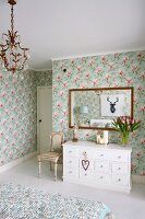 White chest of drawers below framed mirror on floral wallpaper in rustic bedroom