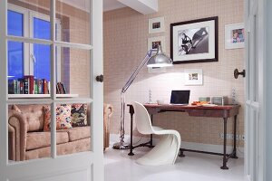View through open door of workspace with white Verner Panton chair and desk against wall next to retro standard lamp