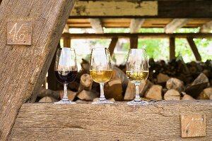 Zwei Rieslinge und ein Pinot Noir vom Weingut Frick auf einem Holzbalken