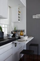 White kitchen counter with small, place-saving pull-out tables