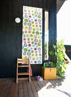 Tripp Trapp chair in front of wall hanging with pattern of colourful circles on black wooden terrace wall