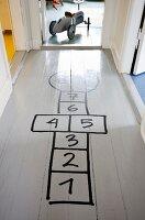 Hopscotch grid drawn on grey hallway floor
