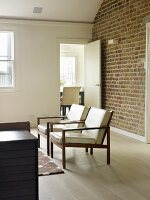 Armchairs with pale cushion on wooden frames in living room with brick wall