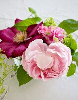 Pink peony and clematis flowers in vase