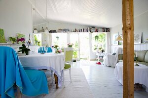 Light blue blanket draped over chair at table with tablecloth in open-plan cottage interior with white wooden floor