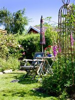 Wooden chair and folding table in summery garden with vintage obelisk and parasol
