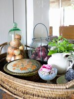 Various containers, onions and herbs on wicker tray