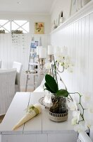 White orchid and candelabra holding white pillar candles on cabinet against white, wood-clad wall