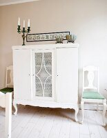 Half-height rustic cabinet painted white flanked by white chairs, all with curved legs
