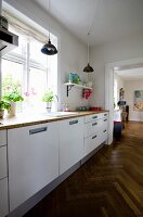 Kitchen counter with white base units below window in renovated period building with continuous herringbone parquet flooring