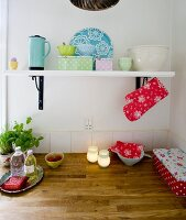 White, wall-mounted shelf of pastel storage jars in country-house kitchen