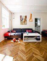 Interior with elegant herringbone parquet floor, modern white coffee table and dark grey sofa combination in corner in renovated period building