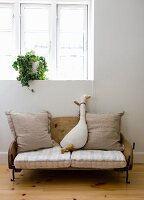 Fabric goose toy sitting on vintage-style children's sofa made from old sledge below window