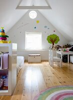 Child's bedroom in converted attic; shelving in front of futon on wooden floor, child's table and chairs against gable-end wall