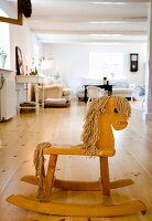 Wooden rocking horse on wooden floor in front of lounge area in rustic interior