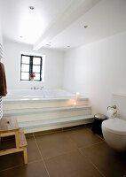 Modern bathroom with brown floor tiles and steps leading to built-in bathtub below window