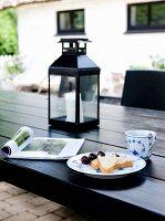 Crockery, magazine and lantern on black wooden table on terrace