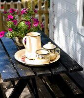 White enamel pots on tray in front of petunia on black garden table