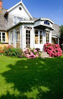 View from garden to house with white wooden conservatory flanked by pink-flowering hydrangeas