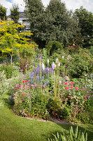 Garden ornaments on rods in flowering garden