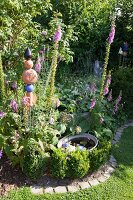 Pale purple foxgloves and garden ornaments in bed edged with paving stones