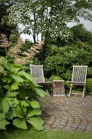 Garden chairs and wooden table on cobbled area