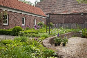 Raised beds edged in low wall outside brick farmhouse