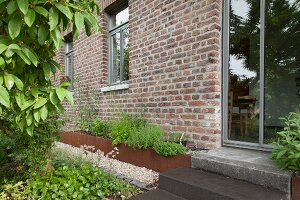 Steps leading to glass door in brick façade next to raised bed with rusty metal surround