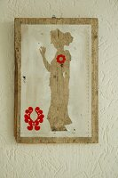 Silhouette-style artwork with red motifs on old wooden board