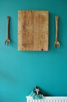 Artistic still-life arrangement of wooden forks and old chopping board on turquoise wall above tiny Flamenco doll sitting on radiator