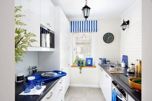 Narrow kitchen with accents of colour provided by blue accessories and striped Roman blind