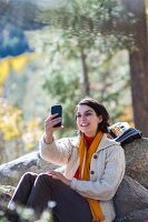 Woman in walking clothes leaning against boulder in autumnal woodland clearing taking selfie