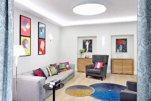 Colourful scatter cushions on grey sofa and armchair, colourful artworks on walls and round rugs on floor